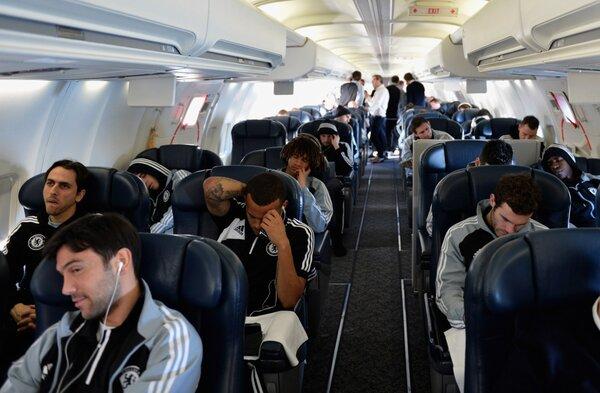 在飞机上,球员们聊天,听音乐
