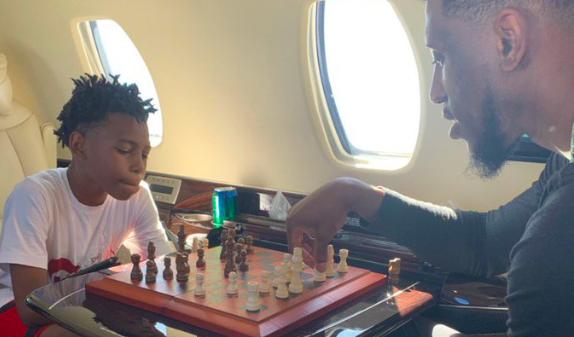 赛迪斯-杨晒与儿子下棋照片:8岁的儿子在教他老爸下棋
