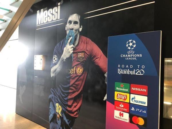 经典!欧冠抽签仪式入口处摆放梅西09欧冠决赛亲吻战靴照